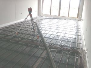 Re-checking the floor levels and preparing to pump the liquid floor screed over the underfloor heating loops.