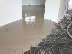 Cemex Supaflo liquid screed starting to flow into the area. As the floor screed is liquid it completely encases the pipework, and by eliminating air pockets found in conventional sand/cement screed increases the efficiency of the underfloor heating system.