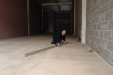 Surveying the site after screeding to check the surface regularity.