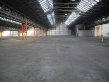 Surveying an industrial unit floor that needs restoration and repair by means of re-screeding.