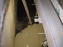 Screeding a basement through a light well using a pumped liquid screed,